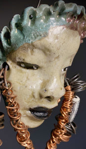I started making art soon after seeing authentic African artwork at the Smithsonian Museum of African Art. I was in total awe.  Dori was inspired by my visit there.  Dori weighs 7 ozs. Her face is formed with hand coiled copper wire and two tribal beads. Dori's face beams with an off white  glaze and black lips.