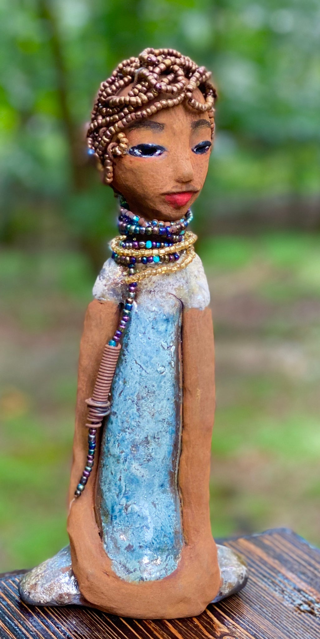 "Meet Morgan! Morgan stands 11.5"" x 5"" x 3"" and weighs 1.11 lbs. She has a lovely honey brown complexion with long loving arms. Morgan has amber gold beaded hair. Morgan dress is metallic gold and blue. She wears a matching gold beaded necklace. Morgan waits to become a part of your one of a kind art collection. Free Shipping!"