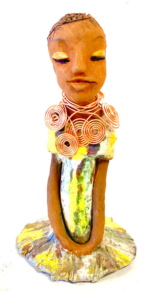 "Meet Trisha! Trisha stands 9.5"" x 5""x 5"" and weighs  1.3 lbs.  Trisha has a lovely glossy yellow  green dress with a copper spiral necklace.   Her hair is etched in clay. Her long arms rest at her side. Trisha is at a special low price. This makes her an excellent starter piece from the Herdew Collection!"