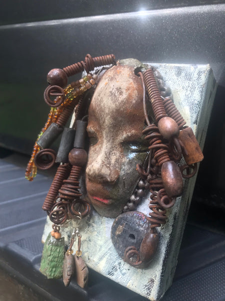 "Meet Monique!      Monique is uniquely mounted on a painted 6""x 6""x 2"" canvas.     She weighs 15 ounces.     Monique's  face is formed with clay, hand coiled wire, raku  beads, textured brown cloth, multi color amber and green beads.     Her face beams with  pale almond white glaze and apple brown lips.  Monique is ready to be hung and seen!"