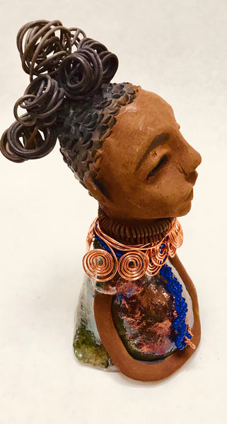 "Darlene stands 8"" x 4"" x 5"" and weighs 1.02  lbs. She has a lovely honey brown complexion with reddish brown lips. She has a short braided hairstyle.  Darlene has a colorful metallic antique copper glazed dress. She wears spiral copper wire necklaces on top of an aqua blue beaded collar. Darlene long loving arms rest at her side. With eyes wide opened, Darlene has hopes of finding a new home."