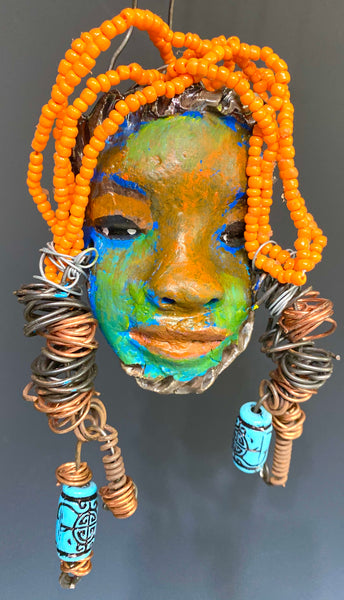 "I started making mask soon after seeing authentic African artwork at the Smithsonian Museum of African Art. I was in total awe. I was inspired by my visit there..  Sophia has a multi colored tone  metallic blue copper gold complexion. She is 7"" x 5"" and weighs 8 ozs. Sophia has  over 50 Mini beads and two tribal beads. Sophia has over 4feet of  copper coiled 16 gauge wire hair."