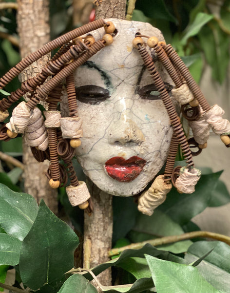 "Larandra has a white crackle complexion. She is 6"" x 5"" and weighs 1.6 lbs. Larandra has over 20 feet of coiled 16 gauge wire hair and several wooden and white raku beads."