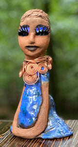"Meet Shawne !  Shawne stands 8"" x 5"" x 3"" and weighs 1.6 lbs.  Shawne has a honey brown complexion with clay hair. She wears long lashes and has a  blue metallic dress.  Shawne has her long loving arms folded as she rest and waits.  Give Shawne a special place inside of your home."