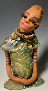 "Meet Sonya! Sonya stands 10"" x 6"" x 4"" and weighs 2.3 lbs. She has a lovely honey brown complexion with  reddish brown lips. She has a braided hairstyle.  Sonya has a colorful metallic green antique copper glazed dress. She wears an awesome antique gold spiral necklace. Her long loving arms rest at her side. With long lashes and eyes wide opened, Sonya has hopes of finding a new home.    Sonya will attract and spark conversation with guest in your home!"