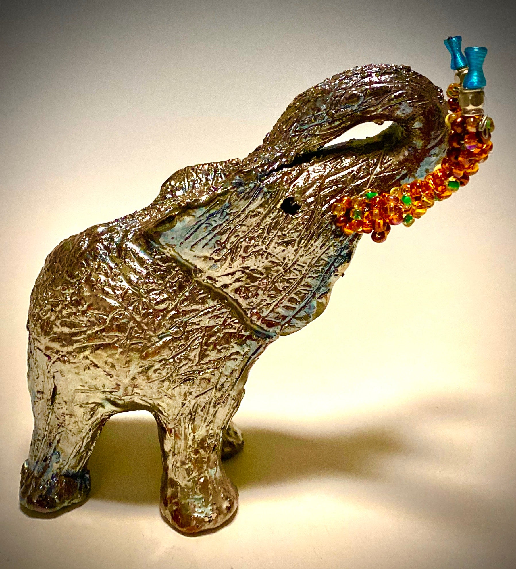 "Raku Elephant Have you HERD!!!!!!  Just one of these lovely Raku Fired Elephant will make an excellent gift for your  friend, sorority or for your home' special place centerpiece.  7"" x 4"" x 4"" 14 ozs. Multi colored beaded tusk Beautiful metallic raku colors For decorative purposely only."