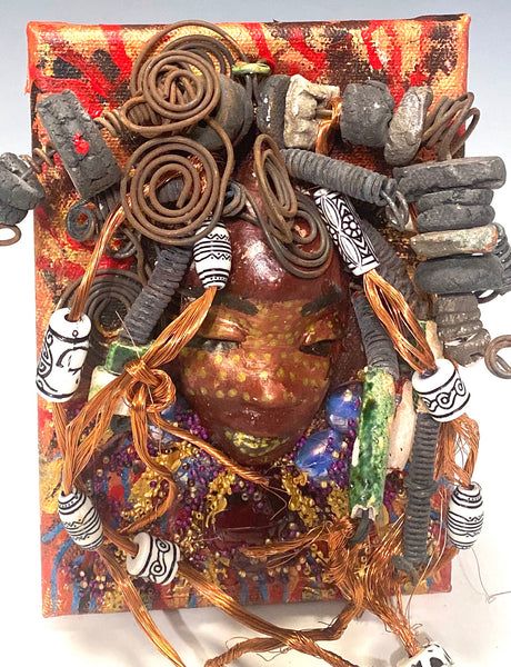 "I started making art soon after seeing authentic African artwork at the Smithsonian Museum of African Art. I was in total awe.  Jamoni was inspired by my visit there.  Jamoni is mounted on a 5"" x 7"" painted canvas. I spent about 3 hours or more just fixing 's hair and attaching beads! Jamoni has over 40 feet of 16 gauge wire, copper wire for hair and over 50 colorful raku beads. Jamoni has a multi red and metallic crackle face with rust golden  lips. Jamoni is ready to be hung!"