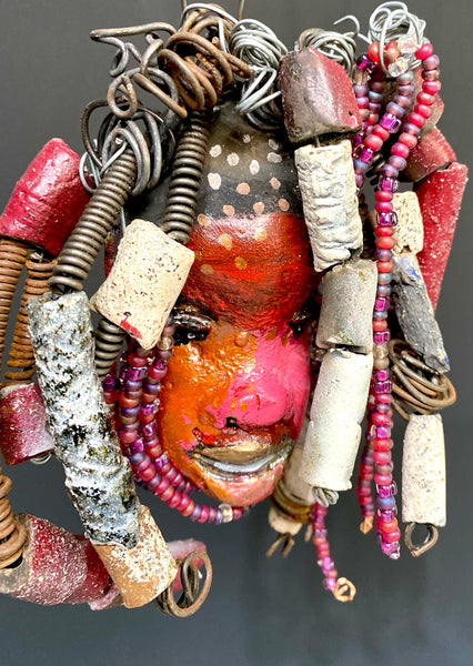 "I started making mask soon after seeing authentic African artwork at the Smithsonian Museum of African Art. I was in total awe. I was inspired by my visit there..  Kylie has a multi colored red tone  metallic copper complexion. She is 7"" x 5"" and weighs 8 ozs. Kylie has  over 50 mini beads and handmade raku beads. Kylie has over 4 feet of 16 gauge wire hair."