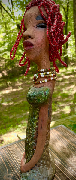"Meet July! July stands 14"" x 5"" x 3"" and weighs 2.05 lbs. July has a head full of red beaded hair. She has a honey brown complexion. July dress has a metallic textured copper green.  She wears a multi colored beaded necklace. With her head slightly turned her long loving arms gently rest at her side."