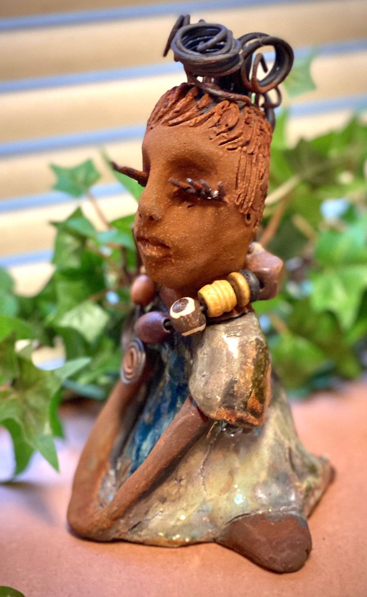 "Janet stands 6"" x 4"" x 4"" and weighs 14 ozs. Janet has a honey brown complexion with wire hair. She wears long lashes and has a alligator green metallic dress. She wears an awesome wood bead necklace. Janet has her long loving arms around her knees as she rest and waits."