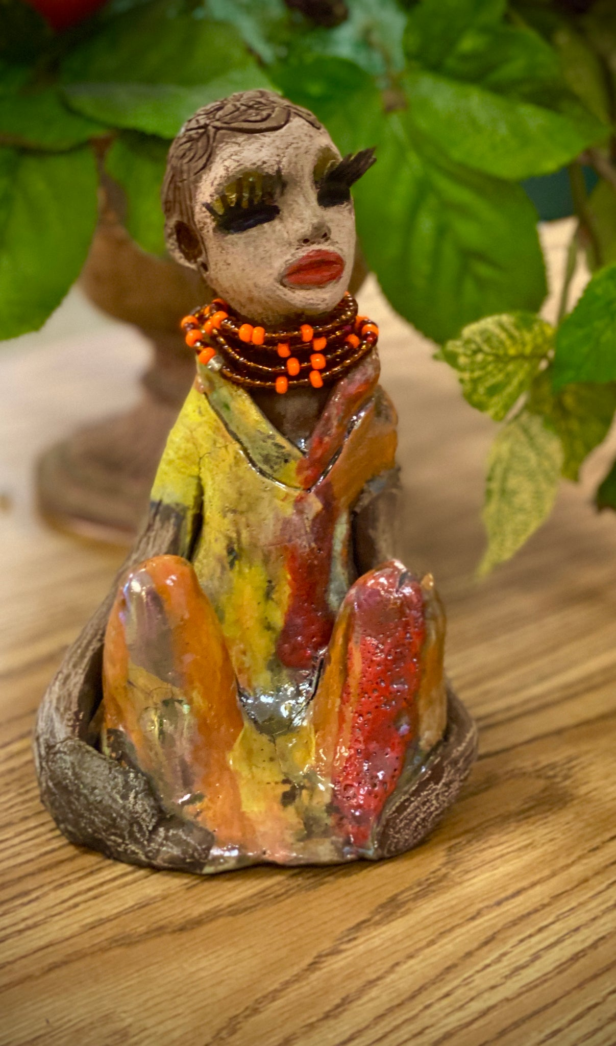 "Valeria sits approx. 7""x 4""x 4.5"" and weighs 1.9 bs. Valeria has her arms nestled beside her knees contemplating her position with some concern . She has a beige colored complexion adorned with long eye lashes and ruby red lips. Her dress is multicolored with glossy metallic yellow red glaze.  A string of orange beads wraps gently around her neck. Her hair is made of etched clay."