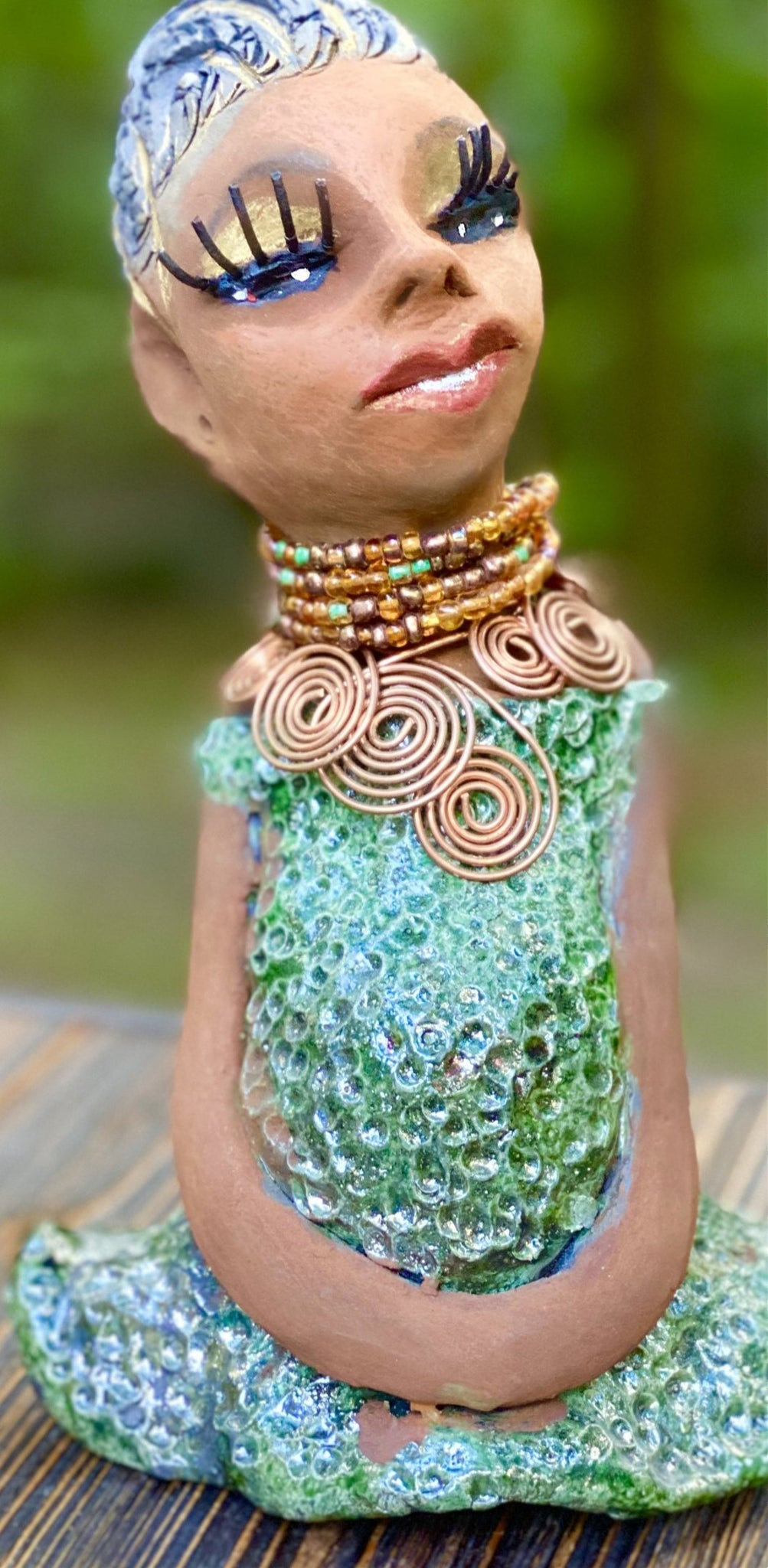 "Meet  Katherine! Katherine stands 9"" x 6"" x 5"" and weighs 1.11 lbs. She has a lovely honey brown complexion with reddish brown lips. She has a braided hairstyle.  Katherine  has a colorful metallic antique copper glazed dress. She wears a spiral copper wire necklaces on top of a multicolored beaded collar. With long lashes and eyes wide opened, Katherine has hopes of finding her way  into your home."