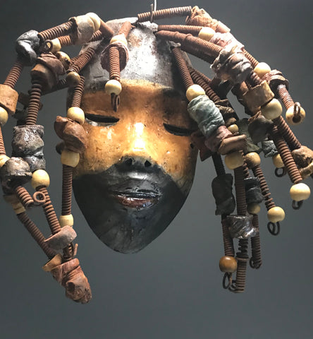 "Meet Zalyn!  I started making mask after seeing an authentic African Mask collection at the Smithsonian Museum of African Art. I was in total awe. Zalyn was inspired by my visit there.       Zalyn has a complexion of  mustard and honey brown.     She is 7"" x 12"" and weighs 1.6 lbs.     Zalyn has over 20 handmade raku fired beads.     She has over 20 feet of coiled 16 gauge wire hair."