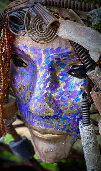 "I started making mask soon after seeing authentic African artwork at the Smithsonian Museum of African Art. I was in total awe. Mansa means she who captures  was inspired by my visit there.  Mansa has a two tone  metallic blue copper gold complexion. She is 7"" x 5"" and weighs 1lbs. Mansa has  over 20 handmade raku fired beads. She has over 50 mini amber bead twisted as hair. Mansa has over 10 feet of  copper coiled 16 gauge wire hair."