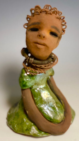 "Meet Nura! Nura stands 7.5"" x 5"" x 5"" and weighs 1.06 lbs. She has a lovely honey brown complexion with  reddish brown lips. She has a wire braided hairstyle.  Nura has a colorful metallic green antique copper glazed dress. She wears spiral wire necklaces  With her eyes wide opened, Nura has hopes of finding  her way into your  home."
