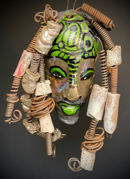 "I started making art soon after seeing authentic African artwork at the Smithsonian Museum of African Art. I was in total awe. This work was inspired by my visit there.  Meet the Green Man! The Green Man is   5""x 6"". He has green and black horizontal stripes with bright eyes and green lips. He has hand coiled 16 gauge wire  hair with over  10 raku beads."