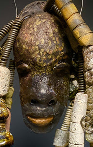 "I started making mask after seeing an authentic African Mask collection at the Smithsonian Museum of African Art. I was in total awe. Juno was inspired by my visit there. Juno is 5""x 3"" and weighs 13.8 ozs. He has a two tone copper and  dark complexion. Juno has over 15 earthy raku beads and over 10 feet of coiled wire!"