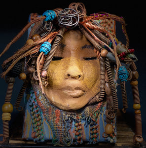 "I started making art soon after seeing authentic African artwork at the Smithsonian Museum of African Art. I was in total awe.  Omaria was inspired by my visit there.  Omaria is uniquely mounted on a painted 5""x 7""x 2"" canvas. It weighs 1.6 lbs. Her face is formed with hand coiled 16 gauge wire, copper wire strands and  textured brown and blue cloth, Omaria's face beams with two tone cocoa brown crackle glaze with earthy lips."