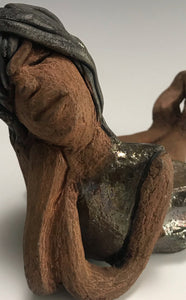 "Meet Ursella!      Ursella stands 5"" x 5"" x 8"" and weighs 1.11 lbs.      She has a lovely honey brown complexion..     Her long loving arms are underneath her face as she ponders.     Ursella dress is a copper glazed and she has hair made of clay.     Ursella is bright eyed and ready to be placed in a good home."