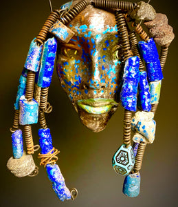 "I started making mask after seeing an authentic African Mask collection at the Smithsonian Museum of African Art. I was in total awe. Trey was inspired by my visit there.   Trey has a two tone complexion of metallic blue and gold. He is 5"" x 7"" and weighs 1 lbs. Trey has over 20 handmade raku fired beads. He has over 10 feet of coiled 16 gauge wire hair. If for some reason Trey does not fit in your home, send him back for a full refund!"