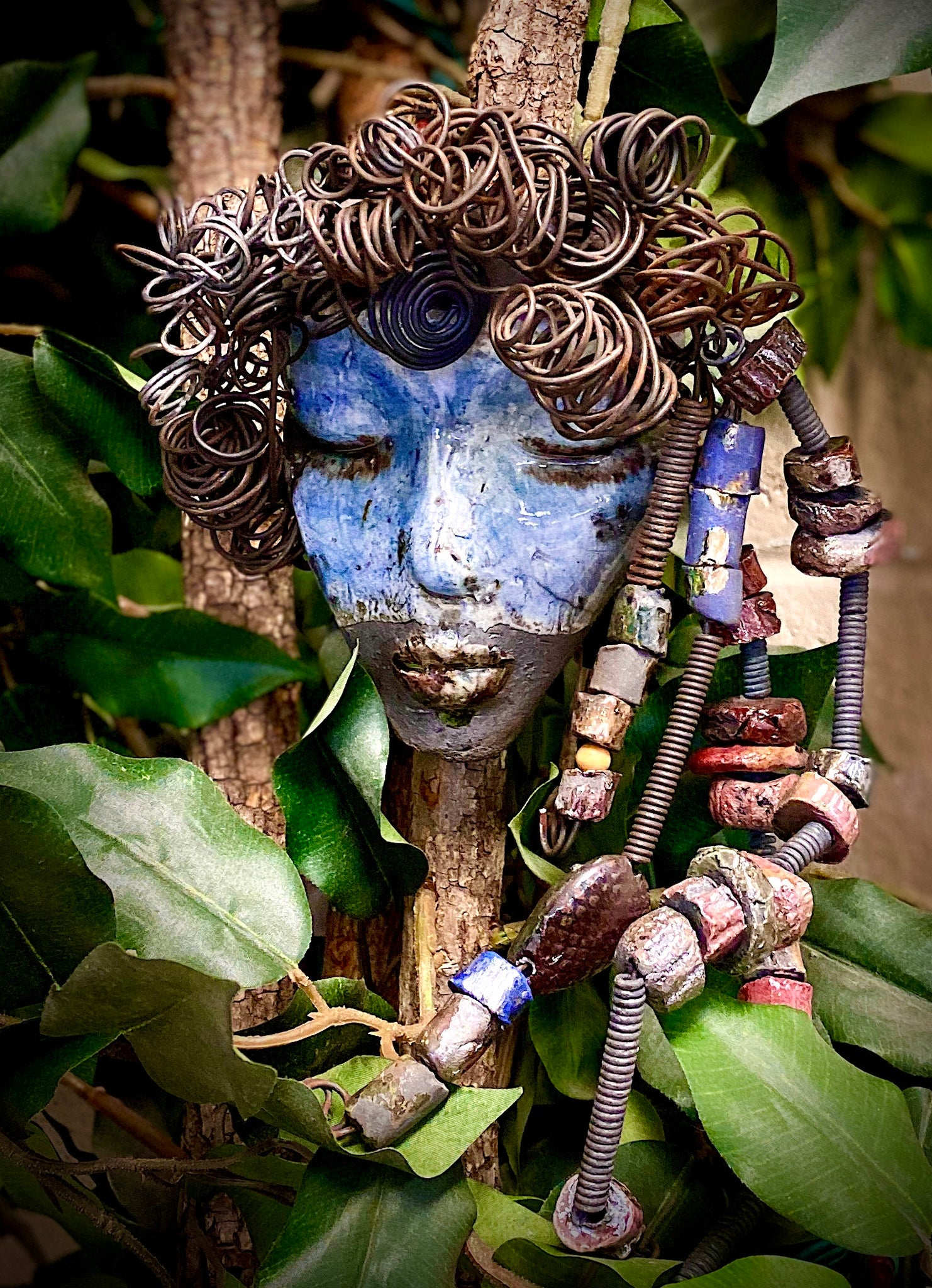 "Sky has a light blue complexion and off white lips! She is 7""x 5"""" and weighs 1.7 lbs. Sky has over 20 handmade raku fired beads. She has over 20 feet of coiled 16 gauge wire hair."