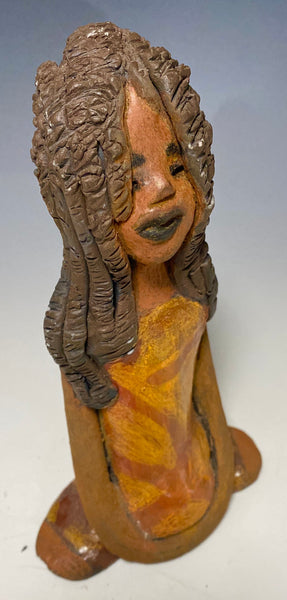 "Meet Bree! Bree stands 7.5' x 4.5"" x 2.5"" and weighs 11 ozs. She has a lovely honey brown complexion. Bree wears a golden brown striped dress. Her hair is smokey black .and made of clay. Bree's long loving arms rest at her side."