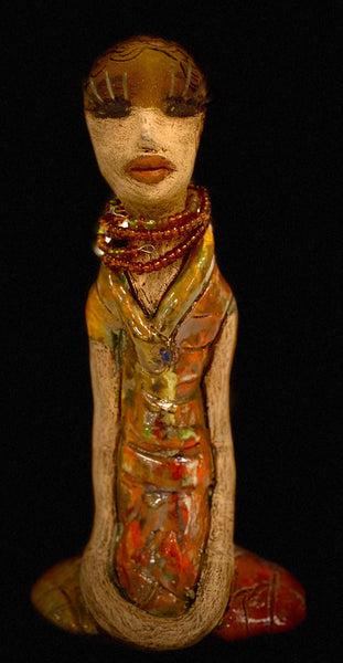 "Desta stands 7' x 4""x 2"" and weighs 1.1 lb. She has bright  dark eyes and a nice honey two tone brown complexion Her long eyelashes and trademark arms resting at her side. Desta dress is a loving glossy orange and yellow mix with copper flashes. Desta originates in African languages and means ""pleasure"". It can be used as both masculine and feminine given names, in the United States it is very rare, though."