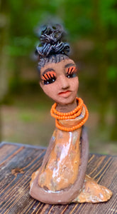 "Meet Abimbola ! Abimbola stands 7' x 4""x 2"" and weighs 1.3 lb. She has bright eyes and a nice honey brown complexion Abimbola  has over 5 feet of 16 gauge wire hair wrapped in a bun. Her long trademark arms rest at her side. Abimbola dress is a loving glossy orange mix with copper flashes. Abimbola is waiting for you to invite her into your home!"