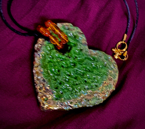 "Have A Heart ! Each heart pendant is handmade with love! It is 3""x 3"" and weighs approx. 3ozs. This pendant has a green and gold metallic raku glazes that renders a unique translucent  patina. The heart is highly textured. It holds a spiral of amber mini beads on a spiral copper wire. This pendant has a nice 12"" black suede cord!"