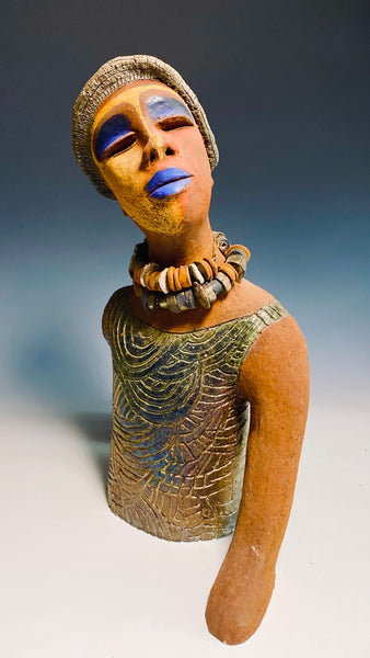 "Meet Blue! Blue stands 18"" x 14"" x 5"". She weighs 6 lbs. Blue has a multicolored face, blue lips and eye shadow. She also has a tribal symbol on her cheek.  A string of raku beads wraps around her neck. Blue showcase a carved asymmetrical pattern throughout her top. Very Exotic & Eccentric!"