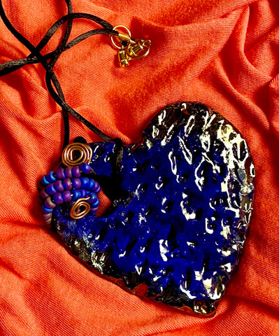 "Have A Heart ! Each heart pendant is handmade with love! It is 3""x 3"" and weighs approx. 3ozs. This pendant has a royal blue and gold metallic raku glazes that renders a unique translucent  patina. The heart  has a textured  pattern. It holds a spiral of off blue violet mini beads on a spiral copper wire. This pendant has a nice 12"" black suede cord!"
