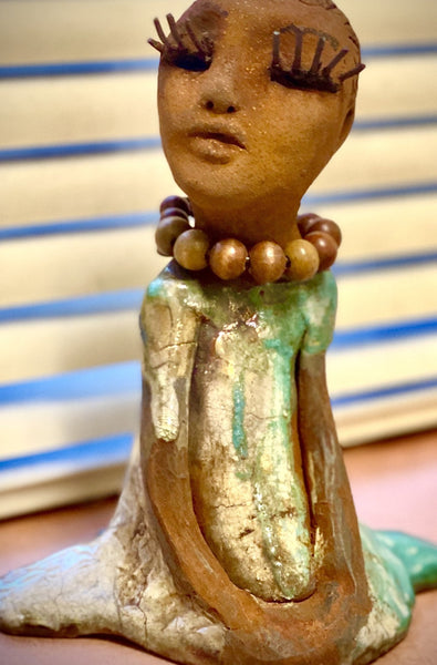 "Tracie stands 6.5"" x 5""x 4"" and weighs  11 ozs.  Tracie has a lovely glossy green dress with a wood beaded necklace.  She has loooong lashes!  Tracie appears to sit in a yoga pose. Her long arms rest at her side."