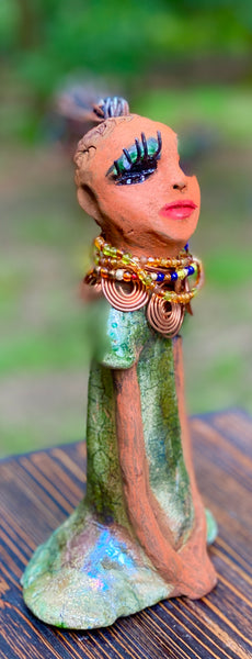 "Kaleesia says yes to wire hair and yes to the Herdew tribe.  Kaleesia stands 9"" x 5"" x 2.5"" and weighs 1.05 lbs.  She has a lovely beige brown complexion with short etched braided clay hair.   Kaleesia  long loving arms rest beside her multicolored copper green dress.  Kaleesia is a sophisticated lady that will grace your home."