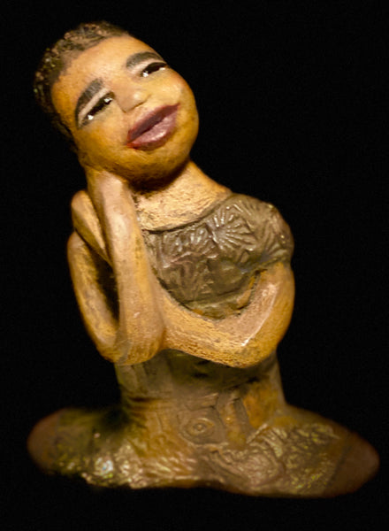 Meet Rae! Rae has a beautiful spirit. She has a honey brown complexion. Her long loving arms are nestled under her face as she gazes. Her braids are made of clay. Rae wears a metallic copper dress. Rae is adorable and deserves a prominent place in your home.