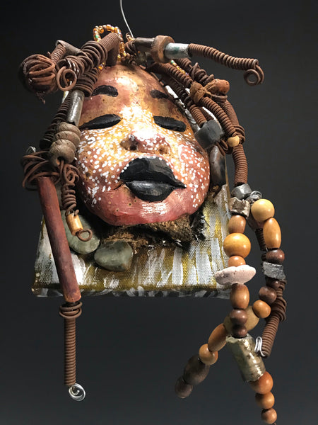 """I started making mask after seeing an authentic African Mask collection at the Smithsonian Museum of African Art. I was in total in awe. Zelda was inspired by my visit there"".       Zelda is uniquely mounted on a painted 6""x 4""x 2"" canvas. It weighs 1.07 lbs.     Her face has white dots over an earthy.glaze with dark lips.     Zelda has hand coiled wire, multi color raku beads,wood beads, and textured earthy rocks..  Zelda is ready to be hung!"