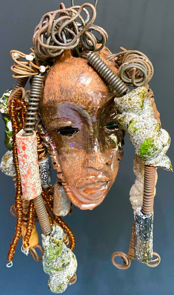 I started making art soon after seeing authentic African artwork at the Smithsonian Museum of African Art. I was in total awe. Cato was inspired by my visit there.  Cato weighs 7 ozs. His face is formed with hand coiled wire, raku beads, and  multi colored beads. Cato's face beams with pale pink crackle glaze and ruby metallic lips.