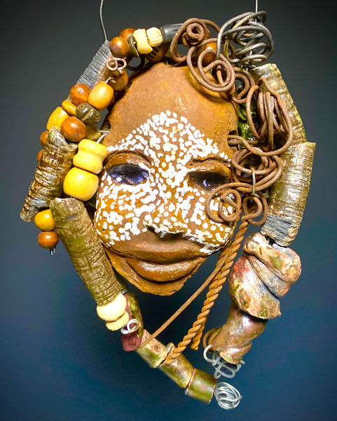 "I started making mask after seeing an authentic African Mask collection at the Smithsonian Museum of African Art. I was in total awe. Rebee was inspired by my visit there.   Rebee has a complexion of l dark chocolate with white  scarified speckles. She is 5"" x 7"" and weighs 11 ozs. Rebee has over 30 handmade raku fired and wood beads. She has over 10 feet of coiled 16 gauge wire hair and 40 raku and wooden beads."