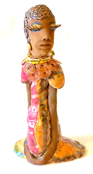 Keeba  long loving arms rest beside her multicolored metallic dress. She wears a spiral copper necklace. Keeba  is a sophisticated lady that will grace your home.