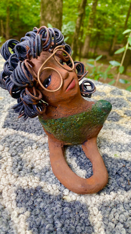 "Meet Elma the Mermaid ! Elma stands 6"" x 8"" x 4"" and weighs 1.07 lbs. Elma has a lovely honey brown complexion. Elma's body has a copper green metallic glaze She has over 25 feet of curly wire hair. Elma looks up in anticipation of being a part of your home!"