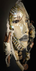 "I started making art soon after seeing authentic African artwork at the Smithsonian Museum of African Art. I was in total awe. Oni was inspired by my visit there.   Oni has an off white complexion with black lips. She is 7"" x 5"" and weighs  1 lbs. Oni has more than 15 handmade raku fired beads. Oni has over 20 feet of coiled 16 gauge wire hair."