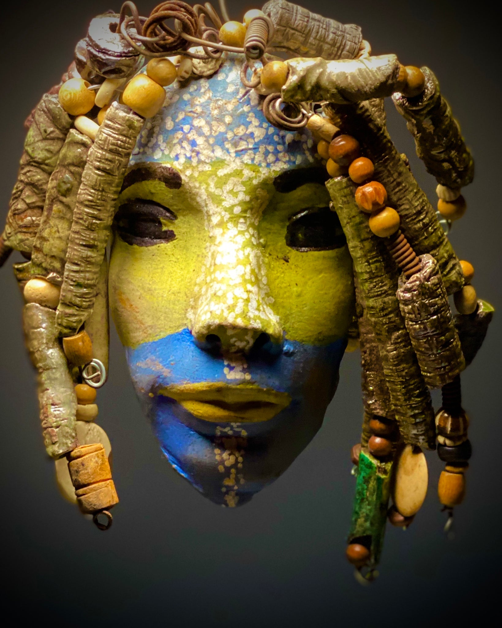 "Peggy has a two tone complexion of light blue and honey yellow. Her face is 5"" x 7"" and weighs 1.8 lbs. Peggy has over 40 handmade raku fired beads. Overall length with hair extension approx 9""x 9"". She has over 20 feet of coiled 16 gauge wire hair."