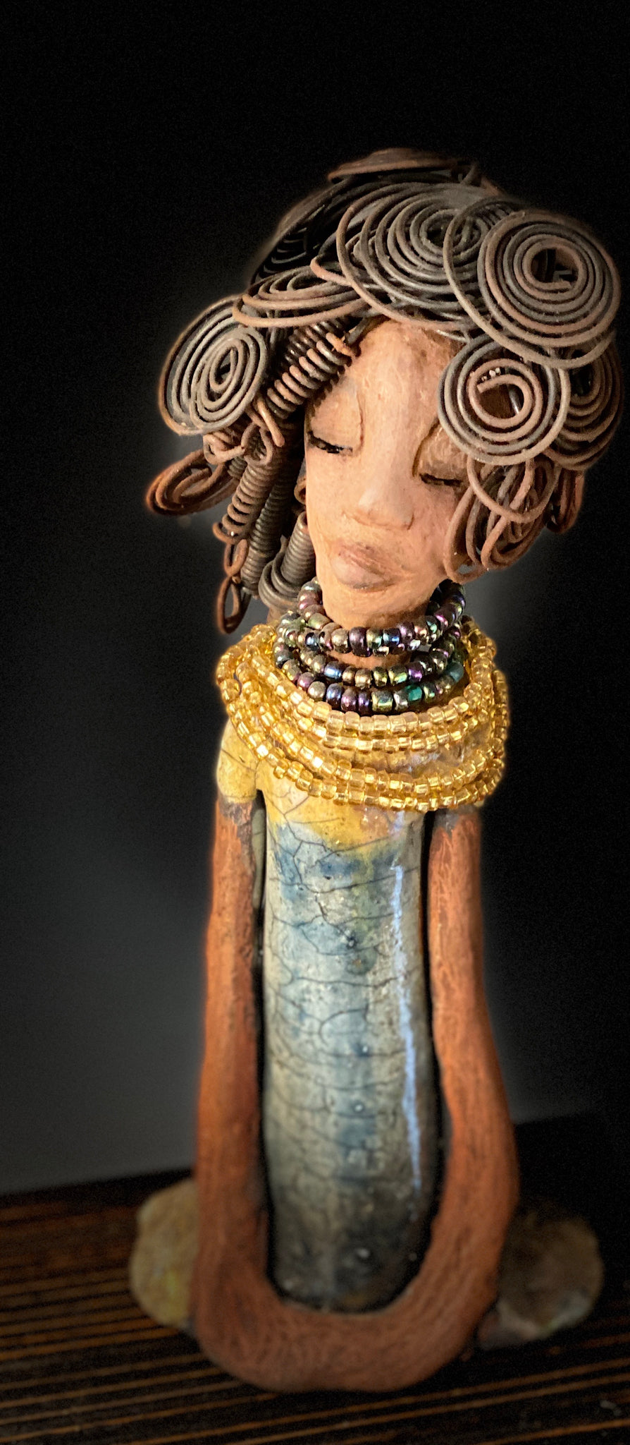 "Sophia knows but will never tell! Sophia stands 10.5"" x 4"" x 3"" and weighs 1.10 lbs. She has a  honey brown complexion with curls, coils and twisted, wire hair. Sophia wears a light blue crackle dress with a dazzling gold and multicolored beaded necklace. Yes, Sophia knows something but she will never tell. Sophia will spark a conversation of ""say what"" in your place."