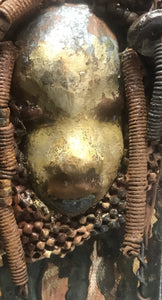 """I started making mask after seeing an authentic African Mask collection at the Smithsonian Museum of African Art. I was in total awe. Dillan was inspired by my visit there"".       Dillan is mounted on a painted 6""x 4""x 2"" canvas. She weighs 15 ounces.     Her face is formed with hand coiled wire, multiple raku, and wood beads, matte textured  and brown cloth.     Dillan's face beams with  almond  green glaze and rust blue brown lips.     Dillan is ready to be hung."