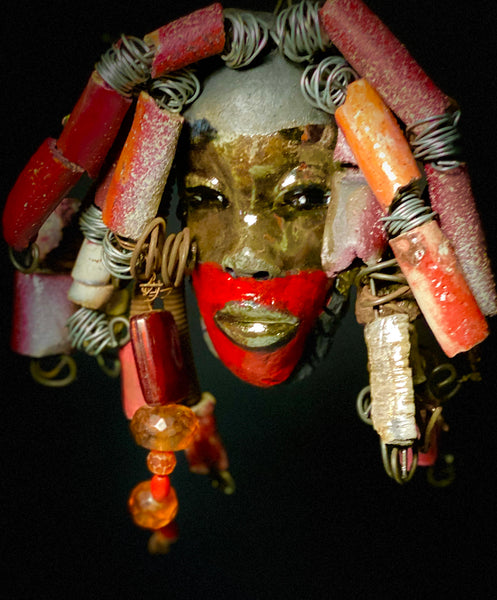 "I started making art soon after seeing authentic African artwork at the Smithsonian Museum of African Art. I was in total awe. Celondo do was inspired by my visit there.   Celondo has a two tone  complexion of fire red and antique copper. He is 5"" x 7"" and weighs ozss. Celondo over 20 handmade raku fired beads. He has over 20 feet of coiled 16 gauge wire hair."