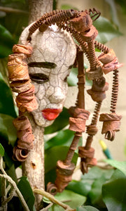 "Emmy has a white complexion and ruby red lips! She is 8""x 5"""" and weighs 9 ozs. Emmy  has over 20 handmade raku fired beads. She has over 20 feet of coiled 16 gauge wire hair."