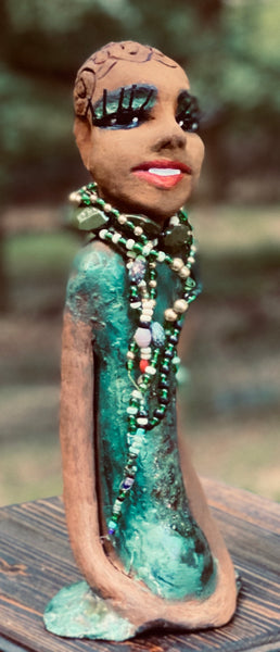 "Meet Makeda What a joy to be around Makeda! She is one of many who has a polite gentle spirit! Makeda 12"" x 6"" x 4"" and weighs 1.1 lbs. Makeda has a lovely honey brown complexion. Her  hair is made of textured clay. She has very loooong eyelashes! She has a  copper green metallic dress. Makeda Is a a young  lady full of pride and joy. If you like sophisticated  sculptures, Makeda will bring joy and peace to your home."