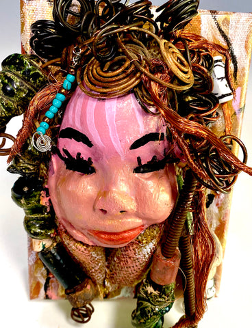 "Peggy has a pink and white complexion with ruby red lips! She is mounted on a  5"" x 7"" and weighs 1.2 lbs. Peggy  has an awesome blue tribal beaded hair dress. She has over 30 feet of coiled 16 gauge wire and copper strands of hair."