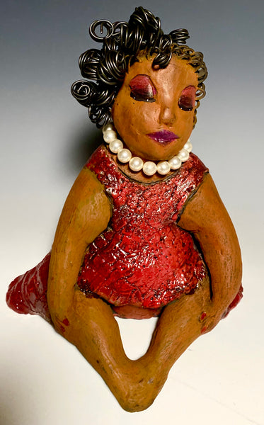 "Odessa is approx. 9""x 9"" x 8"" and  weighs approx. 2.5 pounds. She has her nails polished. Her long loving arms rest at her side. Odessa has a lovly honey rust colored complexion. She wears copper red eye shadow. Odessa's dress is glossy red with etched patterns .  A string of white Swarovsky beads wraps snugly around her neck. Odessa hair is made of curly 16 gauge wire. She got it fixed into a fashionable bun!"