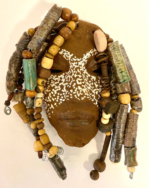 "Carmela has a pattern of light spots on a dark brown complexion. She is 5"" x 7"" and weighs 15 ozs. Carmela has over 40 handmade raku fired beads. She has over 20 feet of coiled 16 gauge wire hair."