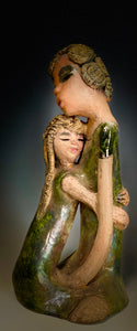 """Hold Me Mama has a very similar look and feel as                             Girl Talk with my Mom"". Hold Me Mama depicts the bond between a mother and child"". They stand 10"" x 5"" x 5"" and weighs 2.8 lbs. Mother and Child has honey brown complexions  with etched copper colored  clay hair. They wear green/ copper raku fired glossy dresses.  Mother assures her daughter  that everything will be alright!"